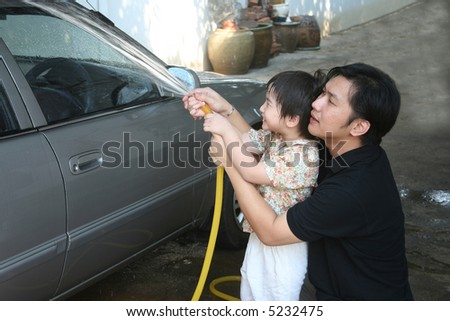 Man and kid washing car in a sunny afternoon happily - stock photo