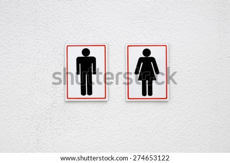 Man and lady toilet sign on white concrete wall background  - stock photo