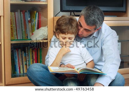 man and little boy sitting on the floor in living room and reading book - stock photo