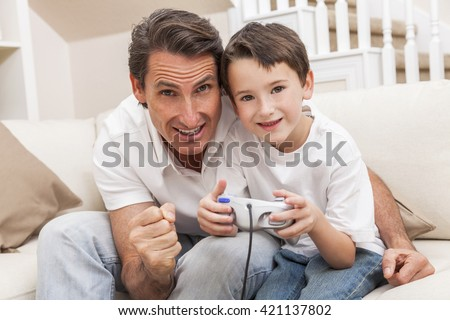 Man and male boy child, father and son having fun playing video computer console game together using handset controller on sofa at home - stock photo
