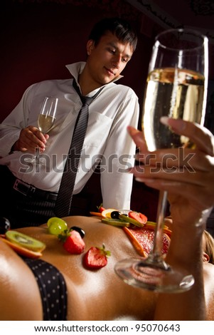Man and naked woman decorated  by fruits with glass of champagne - stock photo