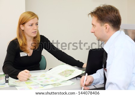 Man and realtor discuss architectural design of apartment in office. Focus on woman. - stock photo