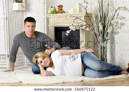 Man and the pregnant woman about a fireplace