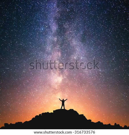 Man and the Universe. A person is standing on the top of the hill next to the Milky Way galaxy with his hands raised to the air.  - stock photo