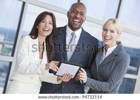 Man and two women, businessman and businesswomen interracial team using tablet computer outside in modern city - stock photo