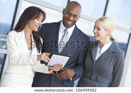 Man and two women, interracial businessman and businesswomen team using tablet computer at work - stock photo