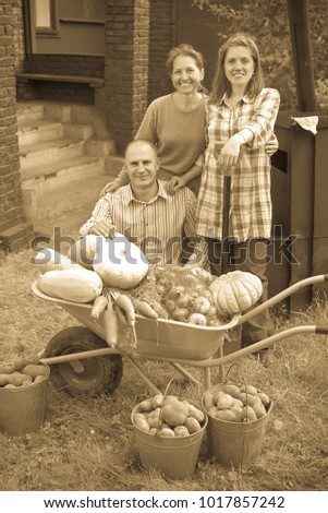 Man and two women with  harvested vegetables in garden