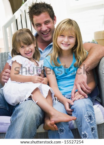 Man and two young girls sitting on patio smiling - stock photo