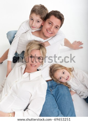 Man and wife posing on the floor with a girl and a boy