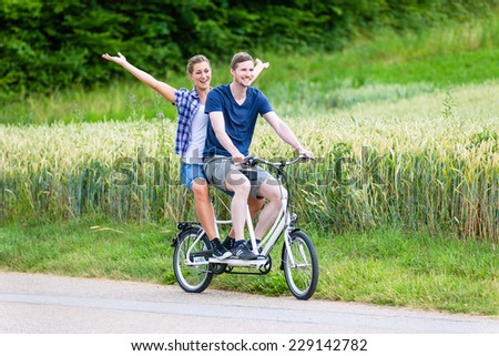 Man and woman, a couple,  riding together tandem bike on country lane - stock photo
