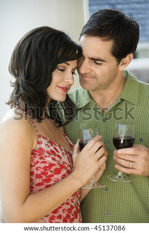 Man and woman act affectionately while holding red wine. Vertical shot. - stock photo