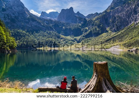 Man and woman admiring the view of the lake Hinterer Gosausee and Dachstein mountains.
