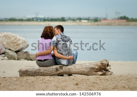 man and woman are kissing at sea beach in the city - stock photo
