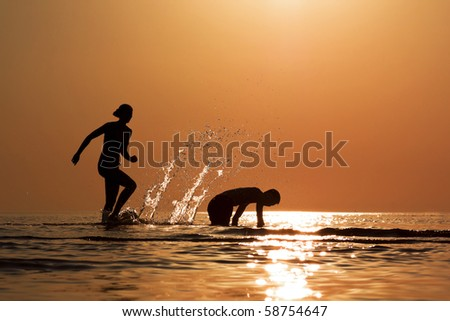 man and woman are playing in the water