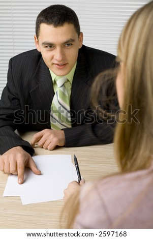 Man and woman at the office desk. Man's pointing paper and talking.