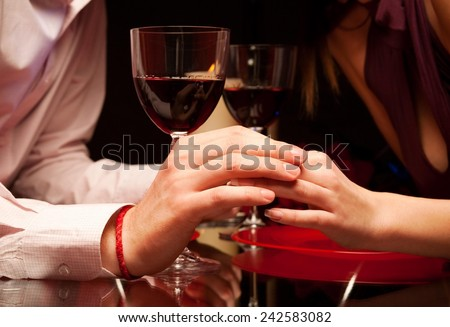 Man and woman at the restaurant - holding hands together - stock photo