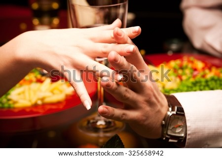 Man and woman at the restaurant - holding hands together. - stock photo