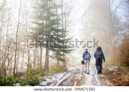 Man and woman backpackers hiking on foggy forest mountain trail in winter/late autumn. Rear view. - stock photo