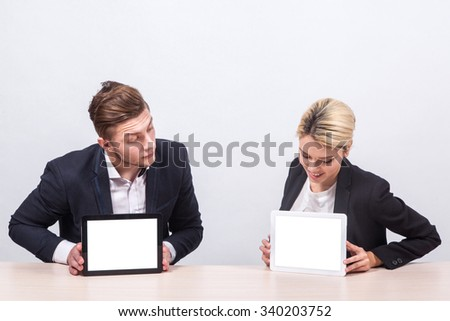 man and woman business people sitting at the table and stare into each other's screens tablets.