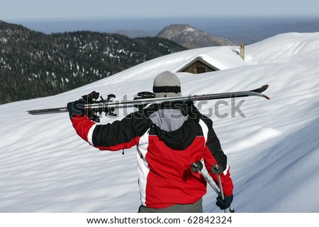 Man and woman carrying skis - stock photo