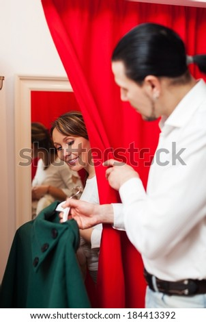 Man and woman choosing coat in fitting-room at market - stock photo