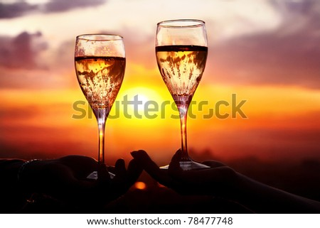 Man and woman clanging wine glasses with champagne at sunset dramatic sky background - stock photo