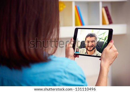 man and woman communicating through video chat on tablet pc - stock photo