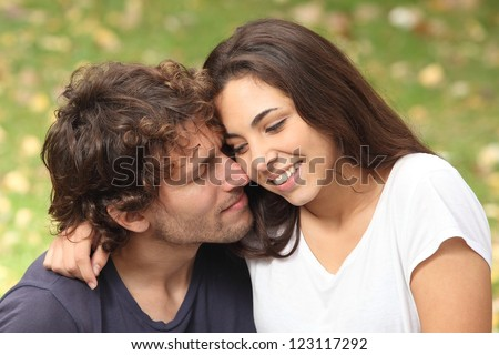 Man and woman couple flirting in a park - stock photo