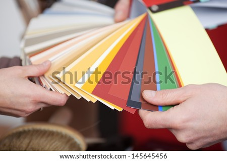 Man and woman discussing new paint colors comparing shades on a set of color cards in a shop - stock photo