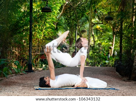 man and woman doing acroyoga in white cloth in the garden - stock photo