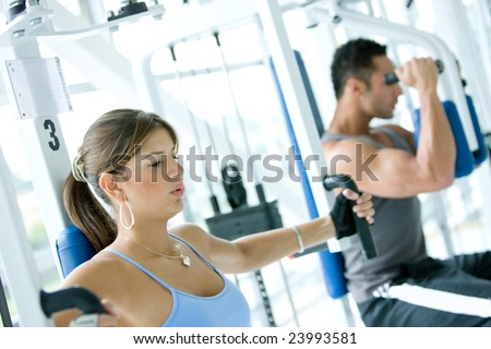 man and woman doing exercises in the gym - stock photo