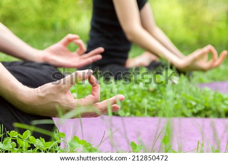 Man and woman doing yoga in lotus position sitting on grass - stock photo