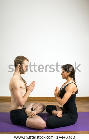 Man and woman doing yoga sitting cross legged facing each other with their eyes closed. Vertically framed photograph - stock photo