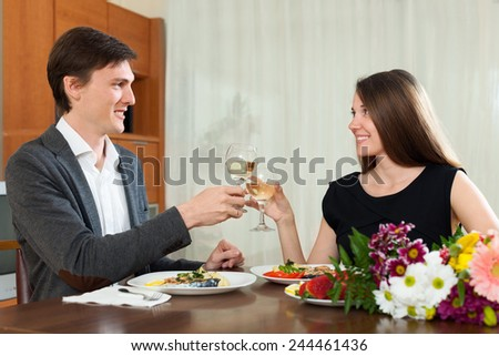 Man and woman drinking champagne at home - stock photo
