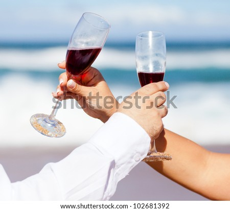 man and woman drinking champagne on beach - stock photo