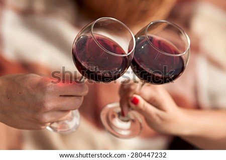 Man and woman drinking red wine. In the picture, close-up hands with glasses. They are celebrating their wedding anniversary. - stock photo