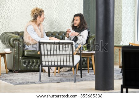 Man and woman during a personal conversation, sitting on a leather couch in a lounge of a stylish retro coffee corner - stock photo
