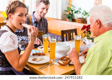 Man and woman eating in bavarian restaurant - stock photo