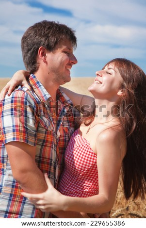 Man and woman embracing and laughing in a field - stock photo