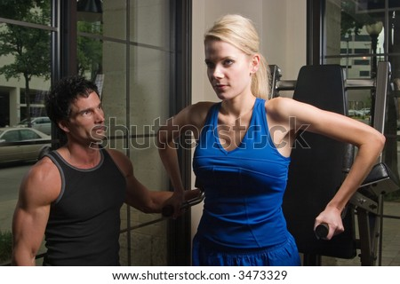 Man and woman exercising together at a fitness center on exercise equipment.  Man could be a personal fitness trainer. - stock photo