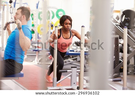 Man and woman exercising using equipment at a busy gym - stock photo