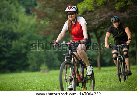 Man and woman exercising with bicycles outdoors, they are a couple in forest