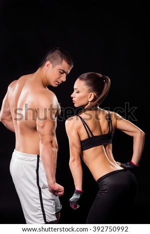 Man and woman flexing triceps. Fitness couple flexing tricep. Look at the proportions. The definition of well-built.