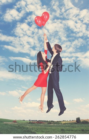 man and woman flying on balloons in the sky - stock photo