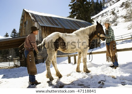 Man and woman grooming a horse on a snowy hillside in the country. Horizontal shot. - stock photo