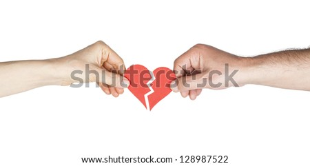Man and woman hands holding broken heart - stock photo