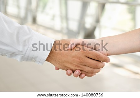 Man and woman  handshake isolated on business background - stock photo