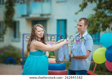 man and woman hanging clothes baby clothes on the rope outdoors - stock photo