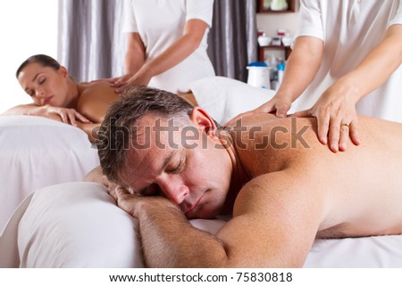 man and woman having massage in spa salon - stock photo