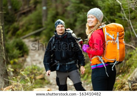 Man and woman hikers trekking in mountains. Young couple walking with backpacks in forest, Tatra Mountains in Poland. Trekking hiking outdoors in beautiful nature - stock photo